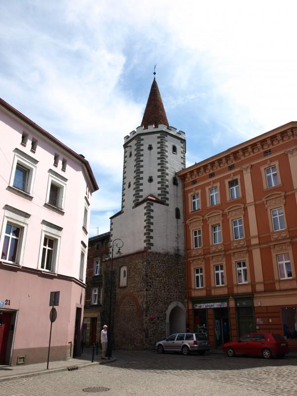 Prudnik posiadał pierwsze umocnienia obronne prawdopodobnie już w XIV wieku. W średniowieczu do miasta prowadziły dwie bramy: górna zwana nyską oraz dolna, przy której w XV wieku, dla wzmocnienia obrony, wzniesiono kamienną wieżę - Wieżę Bramy Dolnej.